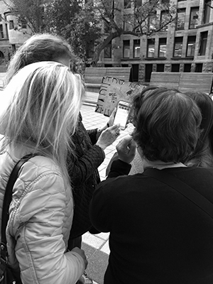 Black and white image of a group from behind working with a map and a cell phone